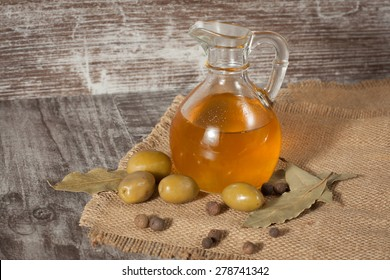 olive oil and olives on a rustic wooden background