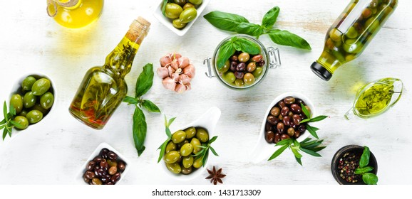 Olive oil and olives on a white wooden background. Top view. Free space for your text.