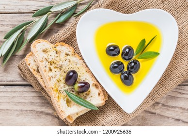 Olive oil and olives, slices of bread on  wooden background. Testing fresh olive oil.