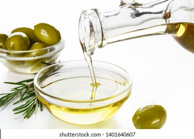 Olive oil pouring from bottle in bowl , fresh olives and rosemary sprigs on white background