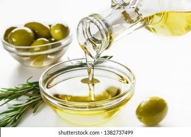 Olive oil pouring from bottle, fresh olives in bowls and rosemary sprigs on white background