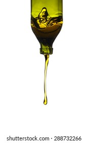 Olive oil pouring from green glass bottle, isolated against white background.