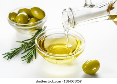 Olive oil pouring from jar, fresh olives in bowls and rosemary sprigs on white background