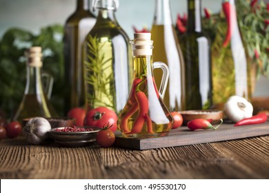 Olive oil and rosemary, chili pepper, many different tomatoes, garlic, red, white, green pepper on old wooden table. Extra virgin olive oil cruets and flavored olive oils with rosemary and chili.