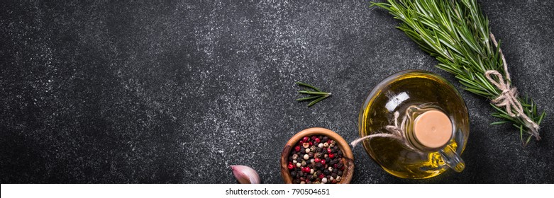Olive oil, rosemary, spices and herbs on black stone table. Long banner format.