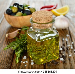 Olive oil with rosemary and spices on a brown table