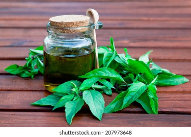 Olive oil in a small container with basil leaves on wooden table
