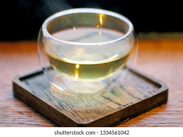 Olive oil in a small dish on a wooden stand with a close-up photo