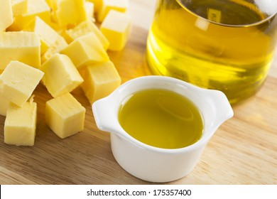 Olive oil in a small glass container with bottle of oil and cubes of butter