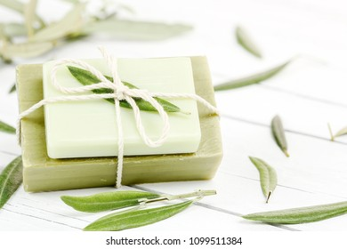 olive oil soap bars on wood with olive tree leaves