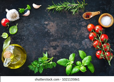 Olive oil, tomatoes, garlic, parsley, basil, spices on dark background
