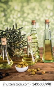 Olive oil, olive tree and green and black olives on a wooden table.