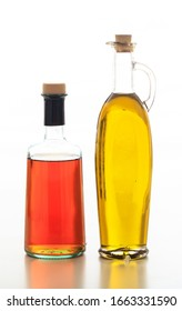 Olive oil and vinegar bottles isolated. Transparent glass bottles with cork stopper isolated against white background. Extra virgin olive oil and red wine vinegar