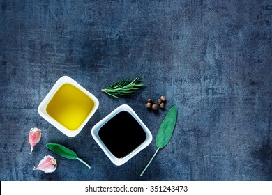 Olive oil and vinegar with peppercorns,  garlic and rosemary on dark vintage background. Top view. Herbs and spices selection. Cooking, Healthy Eating or Vegetarian concept.