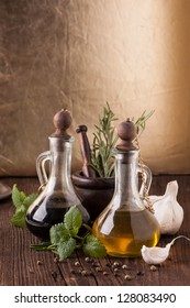 Olive oil and vinegar in vintage bottles on old wooden table with garlic, mint and rosemary in vintage mortar