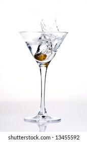 an olive splashing into a martini