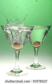 Olive splashing into a martini glass on a graduated green background.