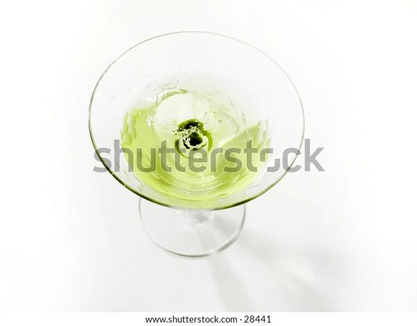 An olive splashing into a martini glass.