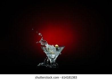 Olive splashing on cocktail isolated on red and black background