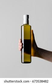 Olive / Sunflower / Sesame Oil Bottle Mock-Up - Male hands holding a oil bottle on a gray background