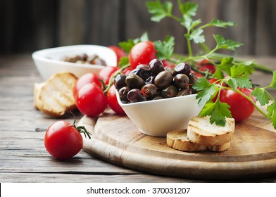 Olive with tomato and parsley on the wooden table, selective focus