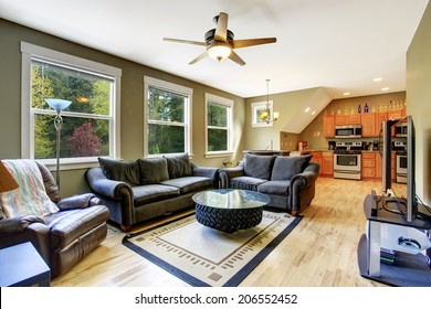 Olive tone living room with dark green sofa and love seat. Creative design of coffee table made of tire and glass top on top of it