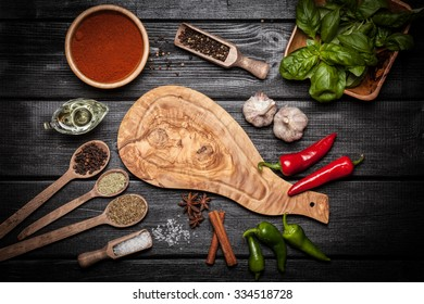 Olive wood board with different spices on wooden surface