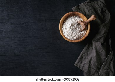 Olive wood bowl with wheat flour and scoop for home baking. With gray textile napkin over black burned wooden background. Top view with copy space