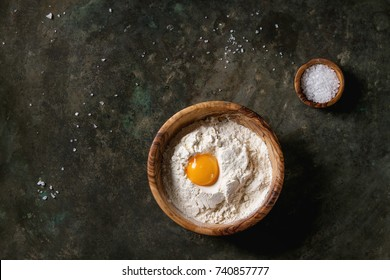 Olive wood bowls with sea salt, wheat flour and whole egg yolk over old dark metal background. Top view with copy space. Baking concept