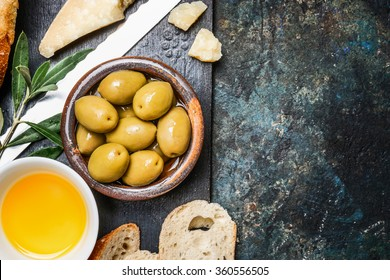 Olives appetizer with cheese, oil and ciabatta gut slices on dark rustic background, top view, place for text. Italian food
