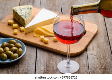 Olives, cheese and red wine. Various types of cheese: Roquefort, Brie, Cheddar and Parmesan. Focus on pouring drink into glass. Food composition on wooden table.