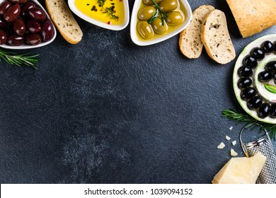 Olives, ciabatta bread, cheese, oil, herbs and spices on black stone background. Mediterranean snacks. Appetizer gourman food. Copy space, top view