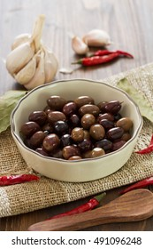 olives in dish on brown wooden background