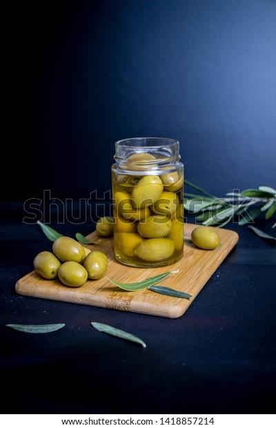 Olives in jar on black background