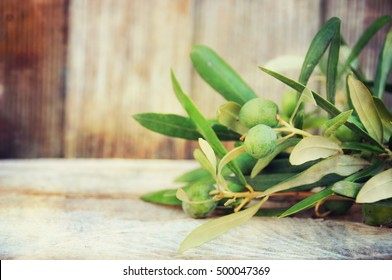 Olives with leaves on a wooden background