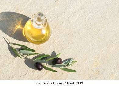 Olives oil and olive branch on a light natural stone background. Mediterranean still life, flat lay with copy space