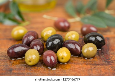 Olives in oil on wooden table.