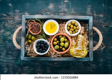 Olives, olive oil, cheese and spices. On a black wooden background. Free space for text.