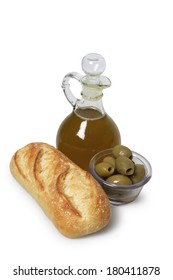 Olives, olive oil, and loaf of bread on white background