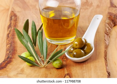 Olives and olive oil on wood background