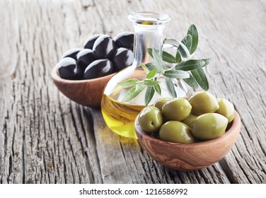 Olives with olive oil on wooden background