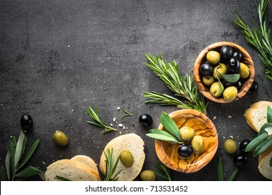 Olives, olive oil rosemary and bread on black slate background. Top view  copy space.