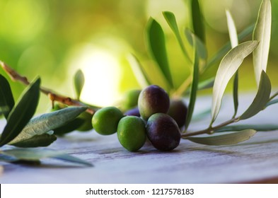 Olives on branches with leaves on table