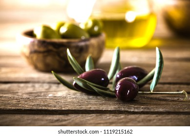 olives on olive branch. Wooden table with olives and olive oil