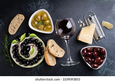 Olives, red wine, ciabatta bread, cheese, oil, herbs and spices on black stone background. Mediterranean snacks. Appetizer gourman food. Top view