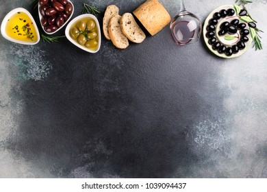 Olives, red wine, ciabatta bread, oil, herbs and spices on black stone background. Mediterranean snacks. Appetizer gourman food. Copy space, top view