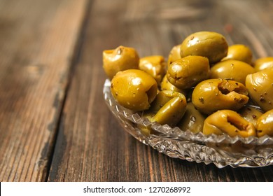 Olives with spices in a crystal bowl on a old wooden table