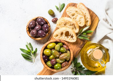 Olives in wooden bowls, ciabatta bread and olive oil bottle on white background. Top view with copy space.