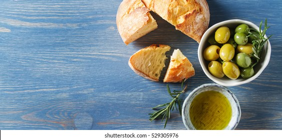 Olivier oil with fresh herbs and bread. Blue background. Italian and Greek national food