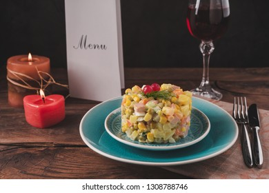 Olivier salad on a blue plate, canteens and a glass of wine on the table.